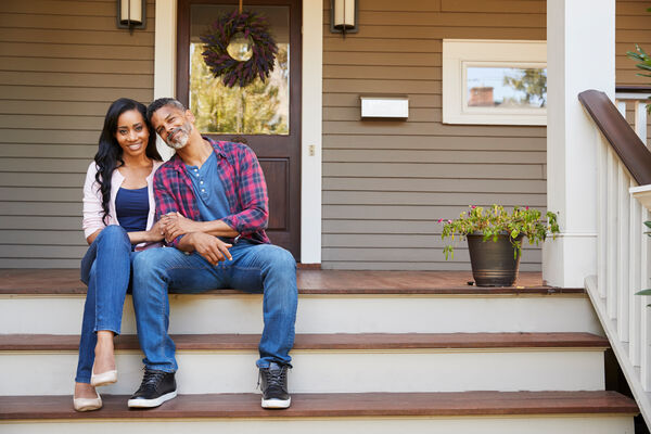 Homeowners on Front Steps of Home